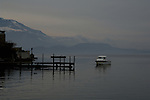 Wooden pier on Zuger see at Zug on a misty morning with the mountains in the background,  Zug, Switzerland.