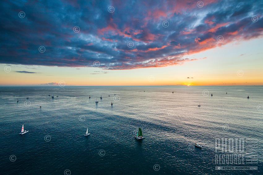Sailboats beneath a beautiful multicolored sunset off the coast of Waikiki, O'ahu.
