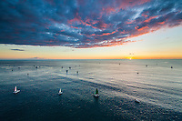 Sailboats beneath a beautiful multicolored sunset off the coast of Waikiki, O'ahu.