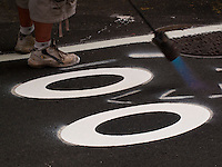 DOT Contractors burn in sharrows and bicycle logo decals into mecadam for the new Thompson Street Bike lane. Once completed the new bicycle lane will link the FIfth Avenue Bike Lane with the crosstown Prince Street Bike Lane and the Grand Street Cycle Track.