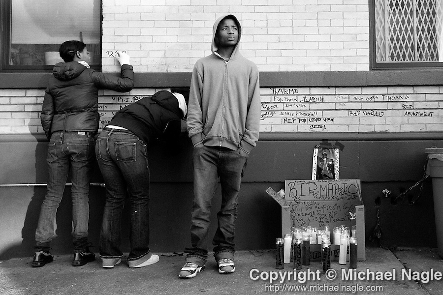 NEW YORK  -  DECEMBER 03, 2008:  Friends visit a memorial in front of 11 Kingston Avenue where 14 year-old Mario Smith was shot to death last night, on December 03, 2008 in Brooklyn.  (PHOTOGRAPH BY MICHAEL NAGLE)