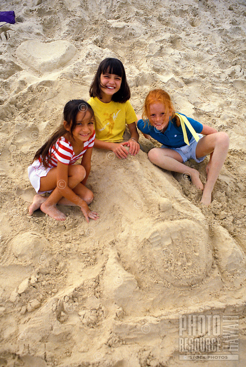 Three girls gathering around a sand car near the beach