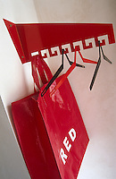 A red carrier bag and hangers are suspended from a metal coat rack