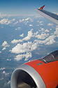 An airplane wing and engine against clouds. The winglet (vertical portion at the end of the wing) is designed to increase fuel efficiency by reducing drag.