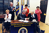 United States President Bill Clinton signs an Executive Memorandum directing federal agencies on the American with Disabilities Act in the Roosevelt Room of the White House in Washington, DC on July 29,1998. Pictured from Left to Right: Becky Ogle, Executive Director of President's Task Force; Tony Coelho, Vice Chair; the President; <br /> US Secretary of Labor Alexis Herman; Justin Dart, Jr.; and US Secretary of Health and Human Services Donna Shalala.<br /> Mandatory Credit: Barbara Kinney / White House via CNP