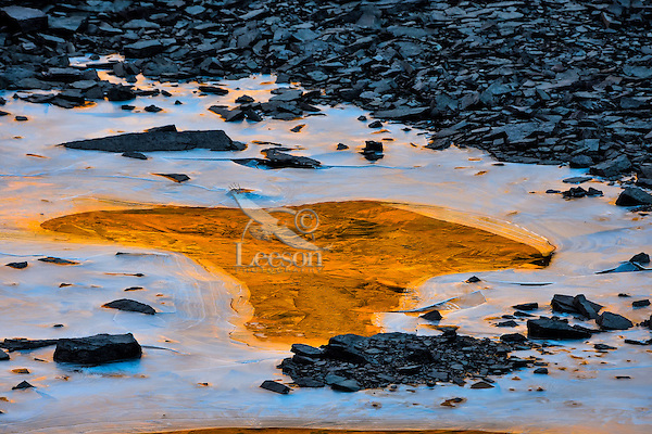 Small ice covered pond in the Northern Rockies reflecting sunrise color from nearby mountains.  Fall.