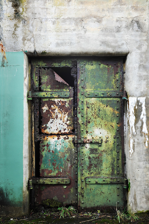 Closed rusty green steel door on concrete bunker tunnel, Artillery Hill, Fort Worden State Park, Port Townsend, Washington, USA