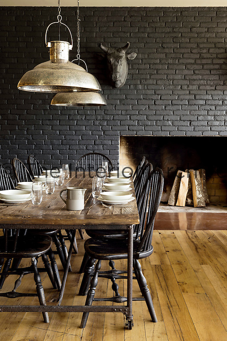 The restaurant is furnished in Shaker style with industrial pendant lights outlined against the black-painted brick of the fireplace