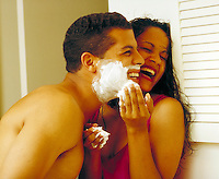Young ethnic playful couple frolicking in bathroom while he shaves. Young ethnic couple. Houston Texas USA.