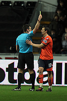 Pictured: Joe Barton of QPR (R) sees a yellow card by match referee Lee Probert (L). Tuesday 27 December 2011<br /> Re: Premier League football Swansea City FC v Queens Park Rangers at the Liberty Stadium, south Wales.