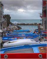 On a cloudy morning in Riomaggiore in the Cinque Terre, boats are lined up in the harbor to protect them from the stormy seas. In summer months, these boats float in the seas most of the time, but spring tends to bring higher winds and storms.