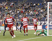 FC Dallas defender George John(14) chases to retrieve the ball after a save by New England Revolution goalkeeper Preston Burpo (24).  The New England Revolution drew FC Dallas 1-1, at Gillette Stadium on May 1, 2010