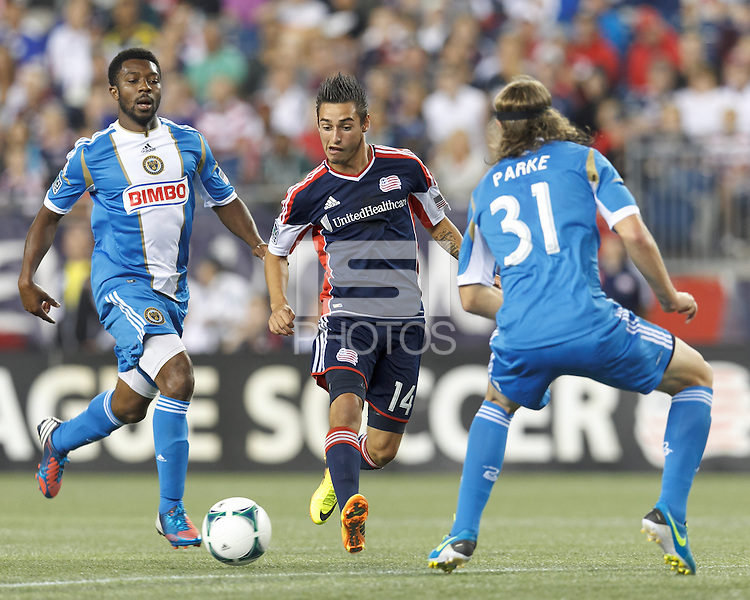 New England Revolution midfielder Diego Fagundez (14) flicks a pass as Philadelphia Union substitute midfielder Michael Lahoud (13) closes. In a Major League Soccer (MLS) match, the New England Revolution (dark blue) defeated Philadelphia Union (light blue), 5-1, at Gillette Stadium on August 25, 2013.