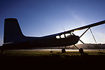 Small airplane backlit silhouetted at sunrise on small landing field