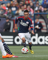 New England Revolution midfielder Diego Fagundez (14) dribbles at midfield.  In a Major League Soccer (MLS) match, the New England Revolution (blue/white) tied Vancouver Whitecaps FC (white), 0-0, at Gillette Stadium on March 22, 2014.