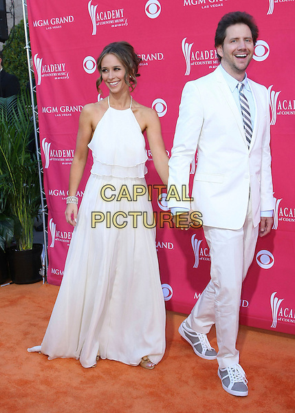 JENNIFER LOVE HEWITT & JAMIE KENNEDY .Country Music Awards held at the MGM Grand Garden Arena, Las Vegas, Nevada, USA, .5th April 2009. .full length white cream dress  suit holding hands halterneck long trainers tie .CAP/ADM/MJT.©MJT/Admedia/Capital Pictures