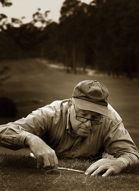 A groundskeeper at a golf course looks through his glasses as he neatly trims the grass on the course