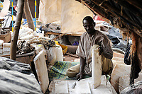 MALI, Mopti, merchant sells salt at market, the salt plate comes by camel caravan via Tombouctou from Taoudenni in the Sahara