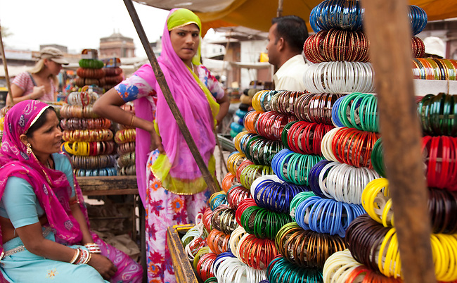 Colourfully clad Rajput women selling tradtitional bangles at the Sardar Bazaar in the centre of the Rajasthani city of Jodhpur, India. Still run by the Maharajah of Jodhpur it is a captivating place dominated by the Maherangarh fort perched on a 125m high hill above the old city. Once known as Marwar, or the Land of Death, the Blue City is now a vibrant , colourful travellers destination dominated by the 16th century fort. Founded in 1459 by Rao Jodha, a Rajput chieftan,  the city grew out of trading profits in sandalwood, dates and copper. Now a chaotic jumble of lanes and open sewers with cattle roaming freely it is a shoppers paradise of brass , furniture, jewellery and spices.