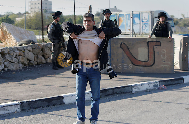 Israeli border policemen check a Palestinian Photographer at the Beit Ainun junction near the West Bank city of Hebron, on April 4, 2016. The man reportedly was arrested within the usual security measures taken in the region by the Israeli forces. Photo by Wisam Hashlamoun