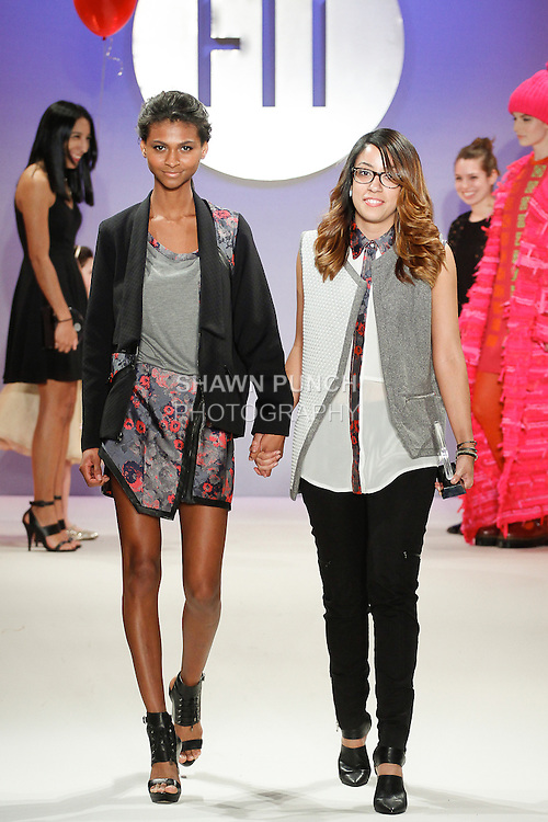 Student fashion designer Talisa Almonte wins a Sportswear Critic Award, and walks runway with model, during the FIT Future of Fashion 2014 Graduates' Collection fashion show, at the Fashion Institute of Technology on May 1, 2014.