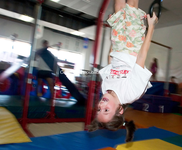 WATERBURY, CT- 05 AUGUST 06- 080506JT03-<br /> Melanie Jillson, 8, of Waterbury, tries to do a flip on the rings at Dynamite Academy of Gymnastics in Waterbury on Saturday, National Gymnastics Day. The academy celebrated the day by putting on gymnastics demonstrations to raise money for children's charities and afterwards opening their courses for children from 18-months-old ot 8-year-olds.<br /> Josalee Thrift Republican-American