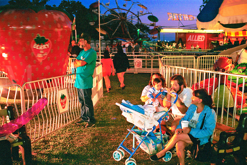 Family takes a break between carnival rides. Family outing. Mother father toddler stroller. League City Texas.
