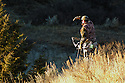 00105-040.02 Bowhunting (DIGITAL) A well-camouflage archer peers over ridge for game. Hunt, prairie, deer. H3A1