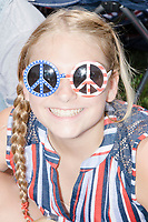 A girl wears American flag-themed glasses in the shape of the peace sign as she watches the 4th of July Parade in Amherst, New Hampshire, on Thu., July 4, 2019.