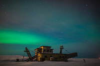 Aurora borealis over a historic dredge outside the town of Nome, Alaska on the Seward Peninsula.