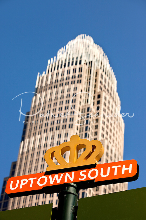 A street sign advertising Uptown South in downtown Charlotte. The Bank of America tower rises in the background.