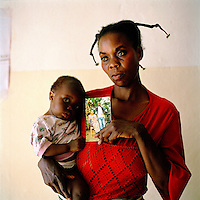 34 year old Mwabe Chantal with her 10 month old child Ngoy Niclette born as a result of rape. She holds a picture of her husband who was murdered by a local militia. An estimated 250,000 women have been victims of sexual violence during the Democratic Republic of Congo's civil war. In the eastern states of the country a recent peace agreement struggles to keep warring factions from fighting, and as the chaos that accompanies war continues, so does the rape of women in the area..©Robin Hammond/PANOS/Felix Features
