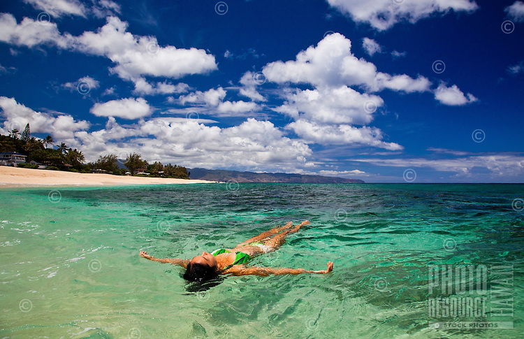 A young woman floats on the crystal blue waters of the North Shore of Oahu