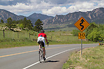 Man cycling on mountain road in Boulder, Colorado. .  John leads private photo tours in Boulder and throughout Colorado. Year-round.