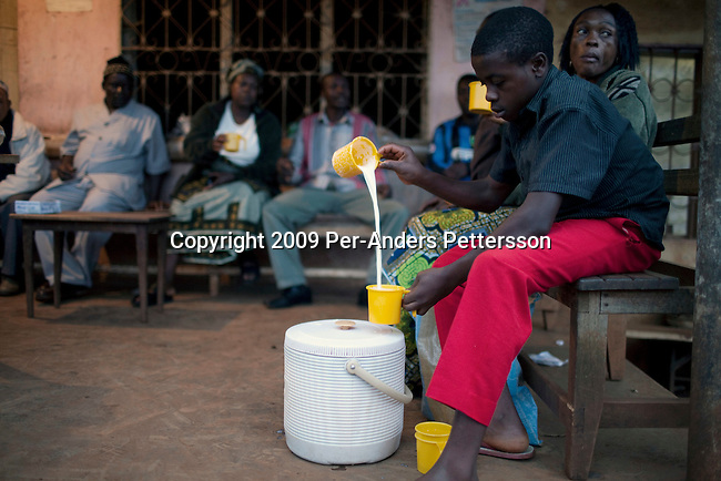 """AKUM, CAMEROON - AUGUST 8: A boy working for the Bamendankwe Farmers Dairy Cooperative Society mixes hot milk at a """"milk drinking spot"""" on August 8, 2009 in Bamendankwe village, Cameroon. In the late afternoon, farmers come with fresh milk to sell. Many regulars come here to have a cup and a chat for about 100 CFA, About 15 Euro cents. Many small farmers in the area are struggling to cope with low milk prices, expensive inputs and competing with low priced milk powder, that is heavily subsidized by European governments and dumped on international markets such as in Africa. (Photo by Per-Anders Pettersson)...."""