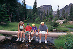Family of four hikers sitting on a bridge near Dream Lake in Rocky Mtn Nat'l Park, CO.