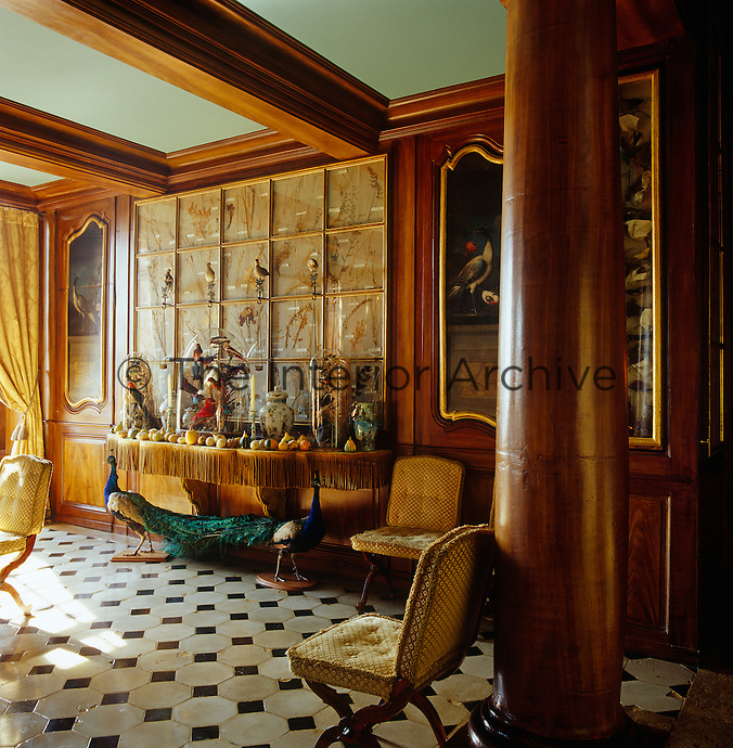 The wood-panelled walls of the dining room are covered with a framed collection of flora and fauna