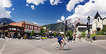 Daytime street panoramic scenery of people in the Town of Banff in Alberta Rockies with Rocky Mountains landscape in the background. Alberta, Canada 2017
