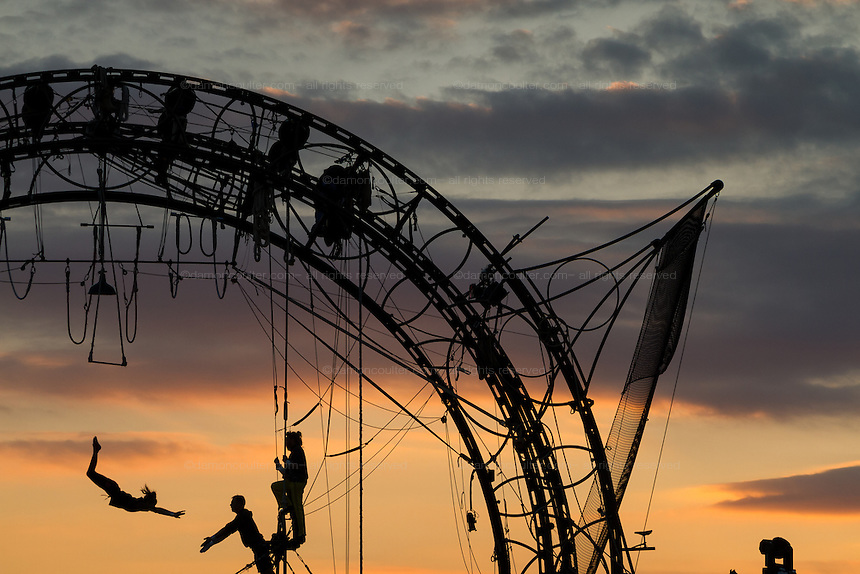 """Trapeze artists from French circus group, Cirk Vost, rehearse for the their final shows  in front of a sunset sky.  Shin Toyosu, Tokyo, Japan. The group performed their  """"Epicycle"""" act, inspired by bande dessinee (Franco-Belgian comics) and Japanese anime. with live music. Performances ran from October 8th to November 6th"""