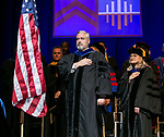 Faculty and staff turn towards the flag during the national anthem Sunday, June 11, 2017, during the DePaul University Driehaus College of Business commencement ceremony at the Allstate Arena in Rosemont, IL. (DePaul University/Jamie Moncrief)