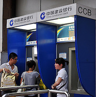 People withdraw money from an ATM of China Construction Bank in Guangzhou, China. The financial crisis won't have too much impact on Chinese consuming market. According to a survey by Nielsen of 50 countries and regions, only 35 percent of Chinese people believed the domestic economy was in a contraction. The figure was the lowest among the 50 world markets..