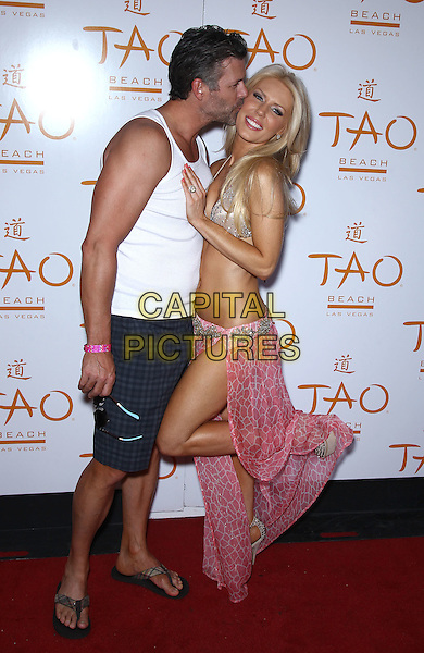 Slade Smiley, Gretchen Rossi.Gretchen Rossi hosts Bling Beach at Tao Beach at the Venetian Las Vegas. Rossi is wearing a custom bikini by Marco Marco, Las Vegas, Nevada, USA, .2nd June 2012..full length hand on hip pink sarong wrap gold bikini  sandals open toe heels barbie name word ring knuckleduster white vest shorts couple knee leg up kissing cheek .CAP/ADM/MJT.© MJT/AdMedia/Capital Pictures.