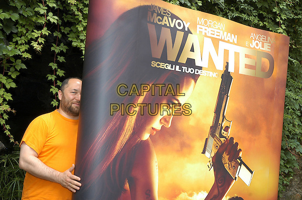 "TIMUR BEKMAMBETOV.Photocall for thhe film ""Wanted"", Rome, Italy..June 11th, 2008.director half length t-shirt beard facial hair orange yellow hiding poster .CAP/CAV.©Luca Cavallari/Capital Pictures."
