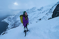 Female hiker on winter ascent of Reinebringen, Moskenesøy, Lofoten Islands, Norway