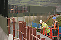 """Workmen make repairs to the """"peace line,"""" a 25-foot high brick, steel and wire structure separating the city's hard-line nationalist and unionist communities, in west Belfast, Northern Ireland, on Wednesday, April 9, 2008. The peace process in Northern Ireland, the U.K.'s third poorest region, culminated last year with the restoration of the province's power-sharing government and the beginnings of an economic boom. Photographer: Paul McErlane."""