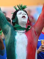 An Italy fan with his nations colours painted on his face and chest cheers his side on before kick off