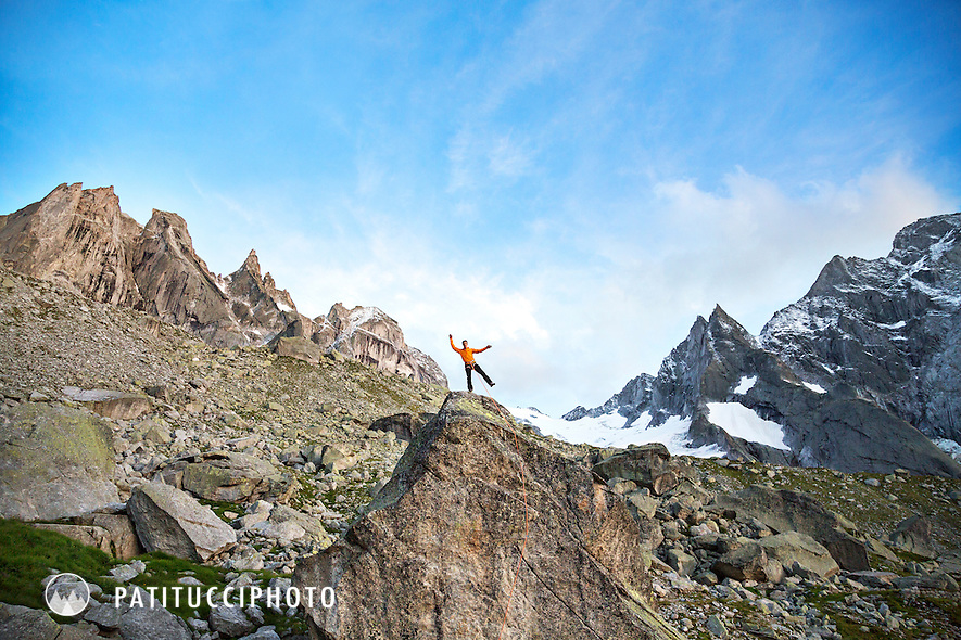 A climber stands on top of a huge boulder celebrating by playfully waving from the top, Sciora group, Switzerland