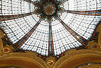 "Central ""Belle Epoque"" coupole in Les Galleries Lafayettes department store.  Stained glass, coupole, guilded arches with wood carvings.  Photo shot from the ground floor looking up."
