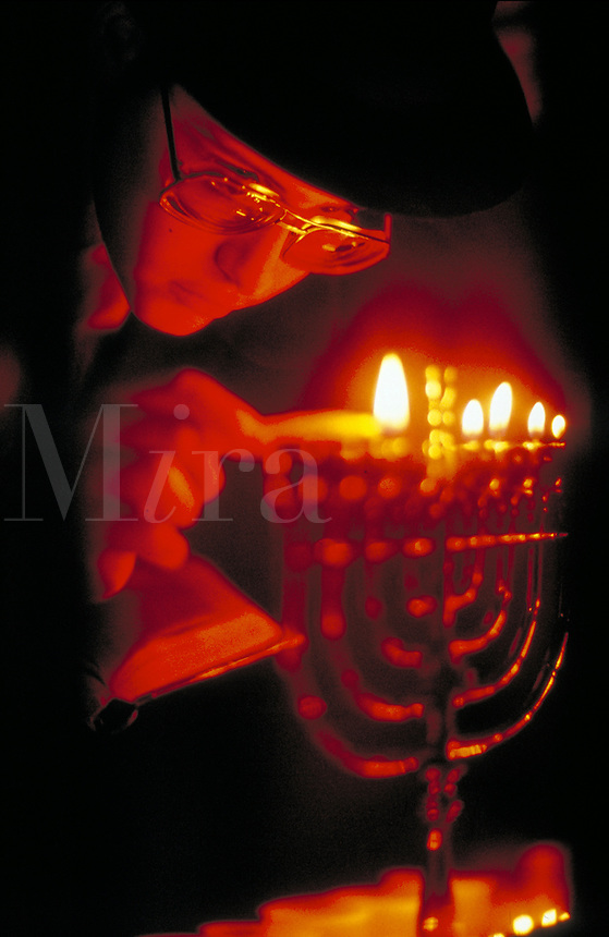 An Orthodox Jewish young man lights the candles on a Menorah. Hanukkah. Judaism. Celebration. People. Jewish young man.