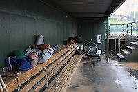 Pitching coach Jerry Nyman (24) of the Lexington Legends finds a quiet spot to take a nap in the dugout during a rain delay before a game against the Greenville Drive on Sunday, July 21, 2013, at Fluor Field at the West End in Greenville, South Carolina. The delay lasted just an hour, and Lexington eventually won, 2-0. (Tom Priddy/Four Seam Images)